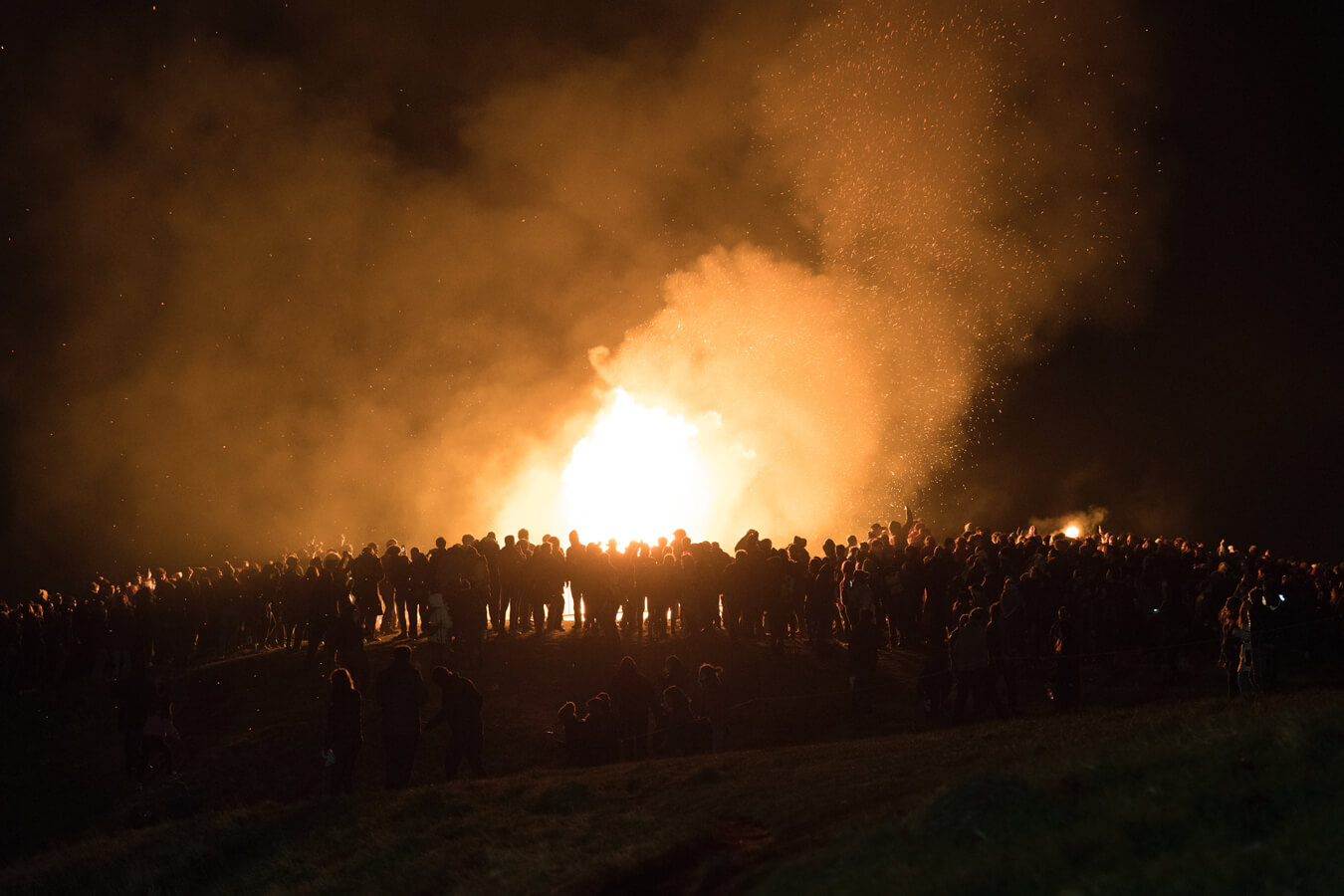 Giant bonfire with people standing around it.