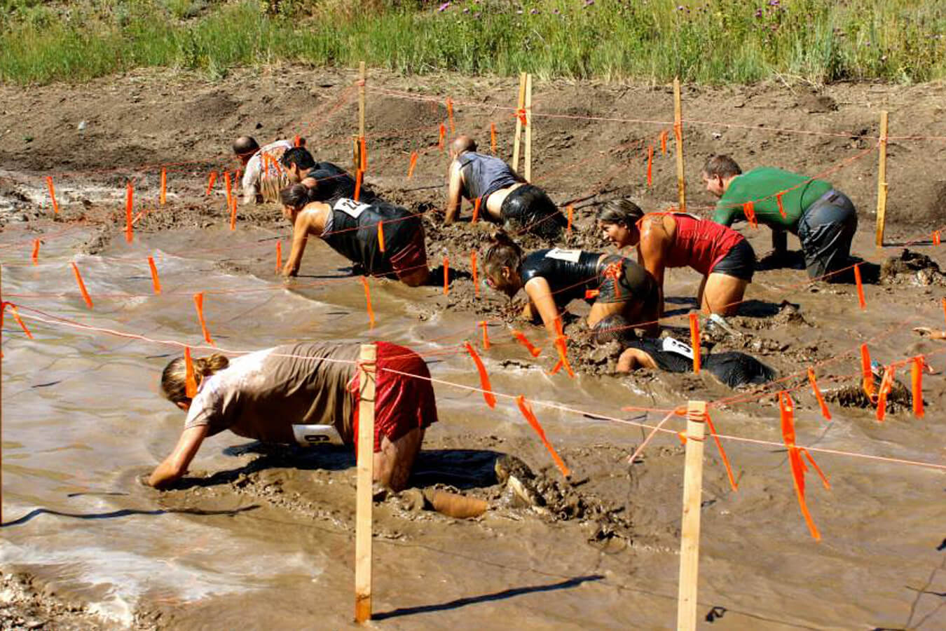 Participants in the Pirate Plunge Mud Run going under the ropes and through the mud